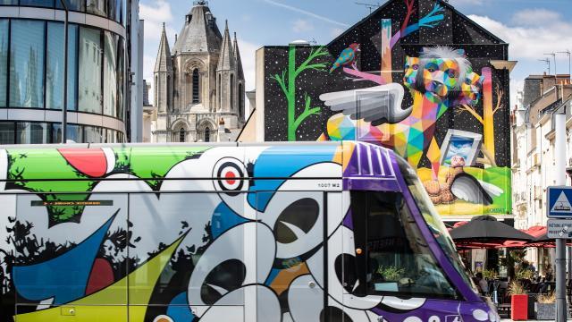 Tramway habillé du thème Les Ecouteurs de Jean Moderne dans le cadre d'Échappées d'Art 2019, devant la fresque Apocalypsis, placette Saint-Aubin et place du Ralliement
