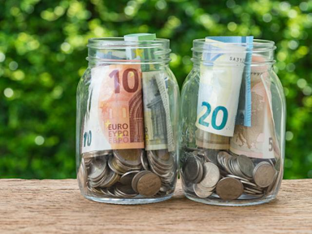 2 glass jar bottles with full of coins and euro banknotes with green bokeh in the background as investment or saving concept.