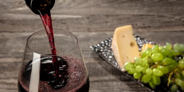 Bottle And Glass Of Red Wine With Fruits Over Wooden Table Min