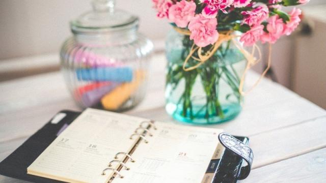 Personal Organizer And Bunch Of Pink Flowers In Vase On Desk