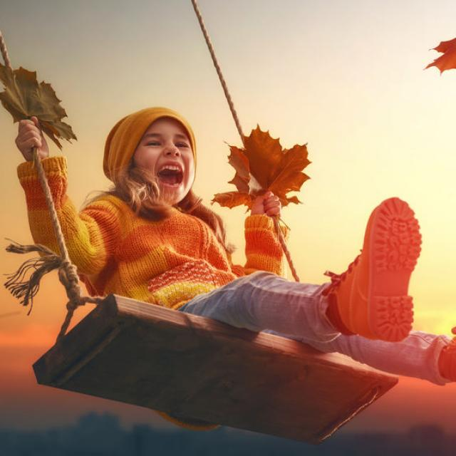 Happy child girl on swing in sunset fall. Little kid playing in the autumn on the nature walk.