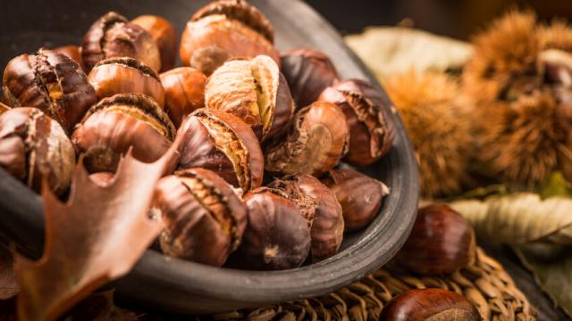 Roasted chestnuts on a rustic wooden table with autumn leaves in the background.