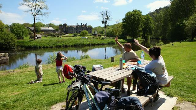 Pause pique-nique lors d'une balade à vélo en famille, devant l'Abbaye de Bon-Repos