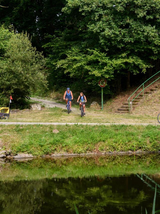 Cyclotouristes se croisant sur le chemin de halage le long du Canal de Nantes à Brest et à la rampe d'accès aux Voies Vertes et à la Vélodyssée, à Pont ar Brost à Carhaix
