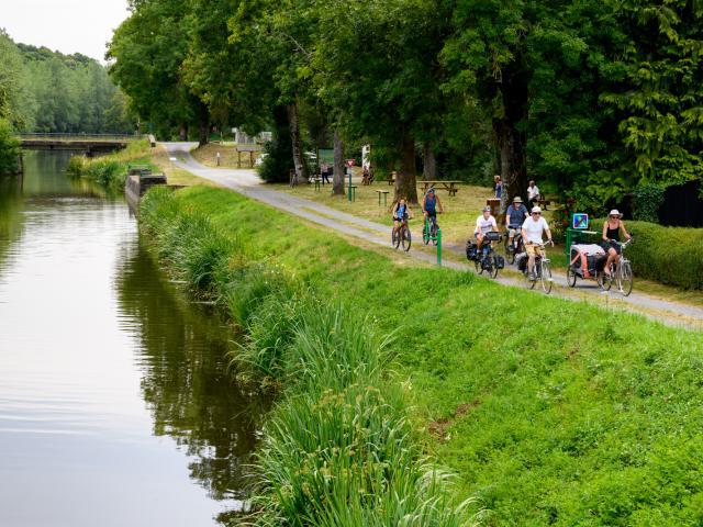 Cyclotouristes roulant sur le chemin de halage le long du Canal de Nantes à Brest, à la jonction avec les Voies Vertes et la Vélodyssée