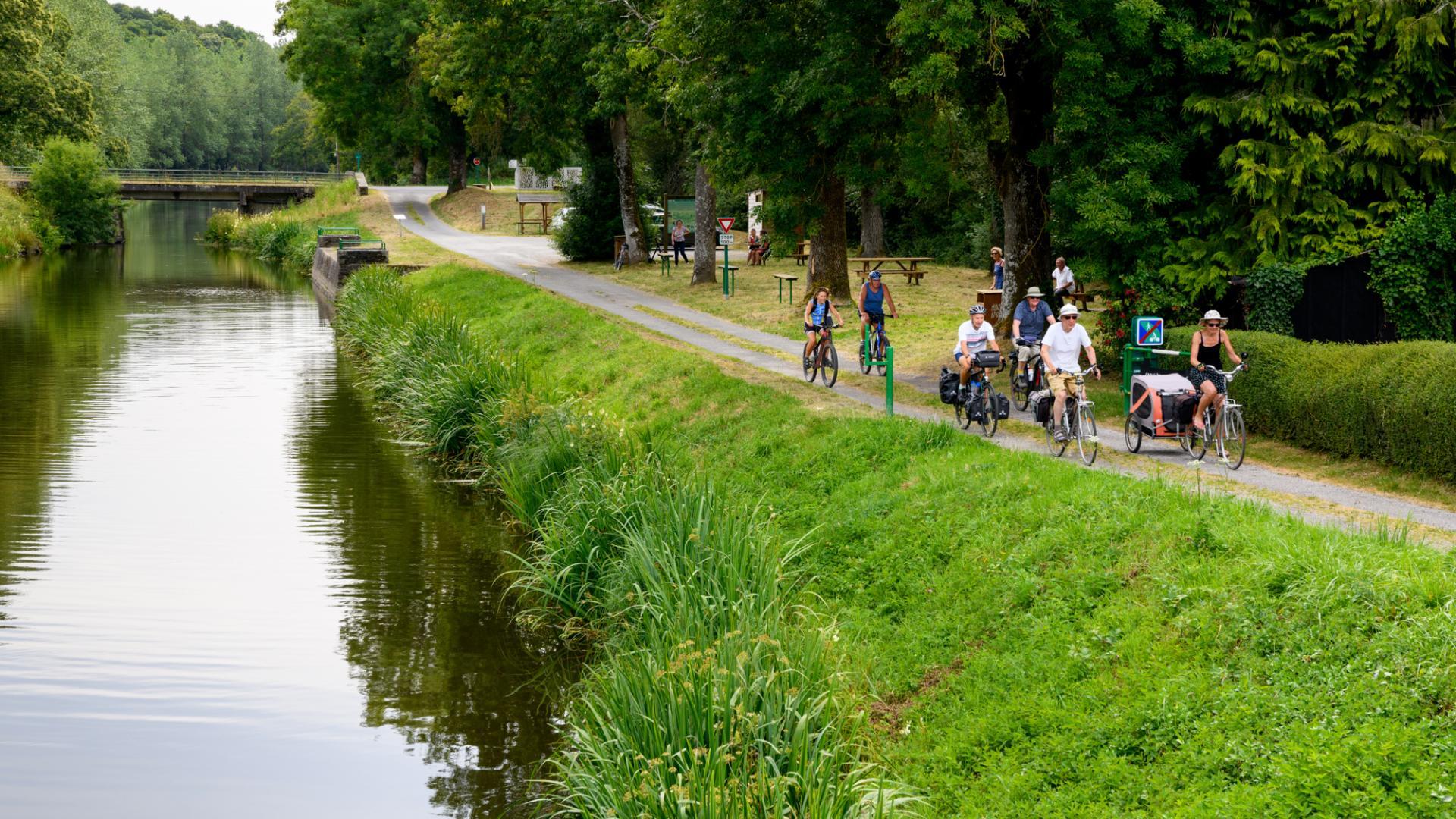 Cyclotouristes le long du Canal de Nantes à Brest. Port-de-Carhaix : jonction avec les Voies Vertes 6 et 7. La Vélodyssée