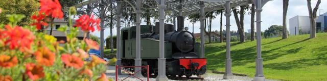 La Locomotive Mallet restaurée avec une statue d'un cheminot à son bord, sous son auvent de type art-déco, Place de la Gare à Carhaix