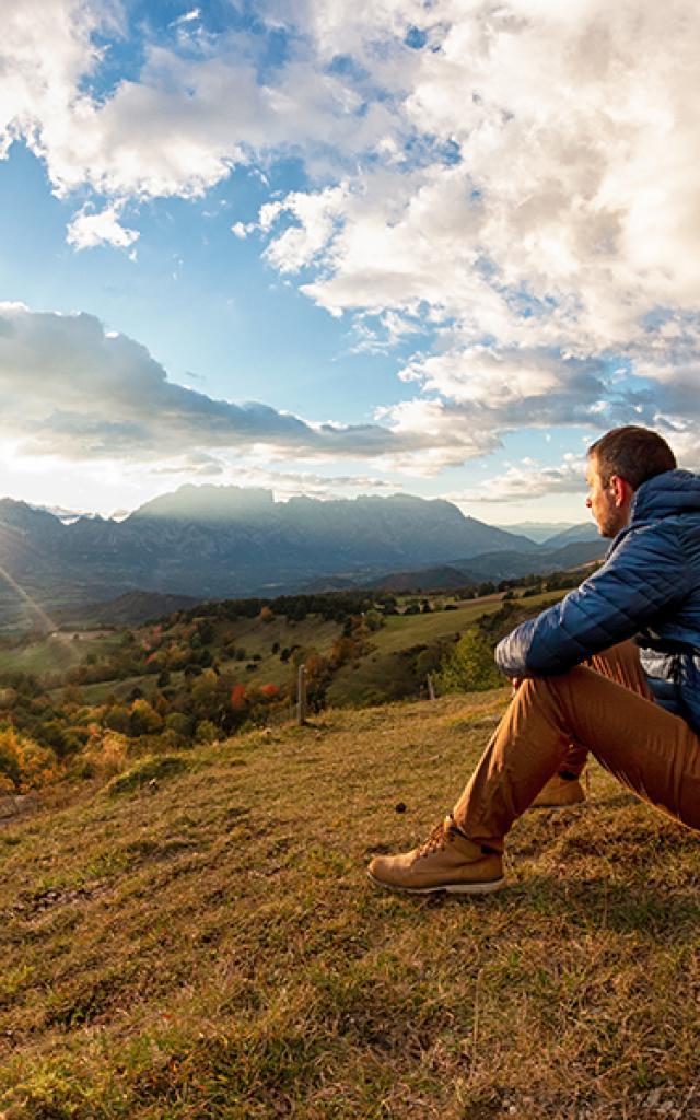 Homme face à la vallée du Champsaur au soleil couchant