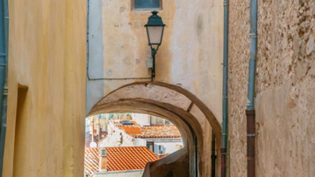 View of a little narrow street with an arch in the town of Brignoles in Provence, south of France