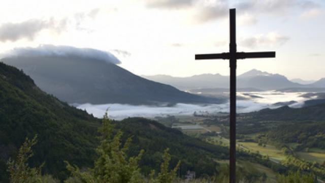 Petit chemin menant à une croix dans la montagne à l'aube, brume dans la vallée, montagnes dans le lointain, La Beaume, Hautes Alpes, France, Août 2018