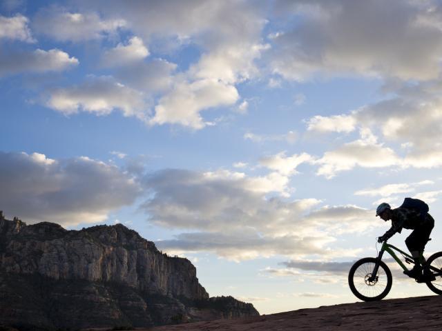 A man rides his enduro-style mountain bike at sunset in Sedona, Arizona, USA.