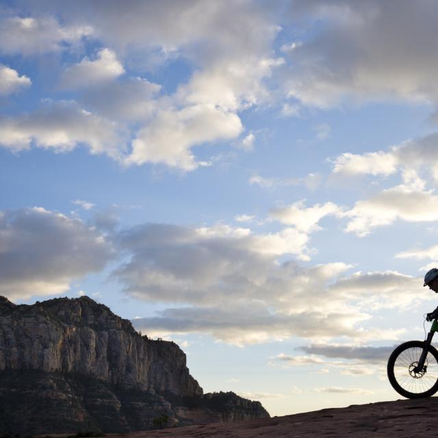 A man rides his enduro-style mountain bike at sunset in Sedona, Arizona, USA.