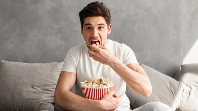 Single man 20s sitting on sofa in gray apartment and eating pop corn, while watching tv in morning