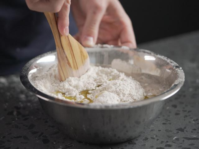 man mixing wet ingredients into flour in steel bowl on concrete countertop