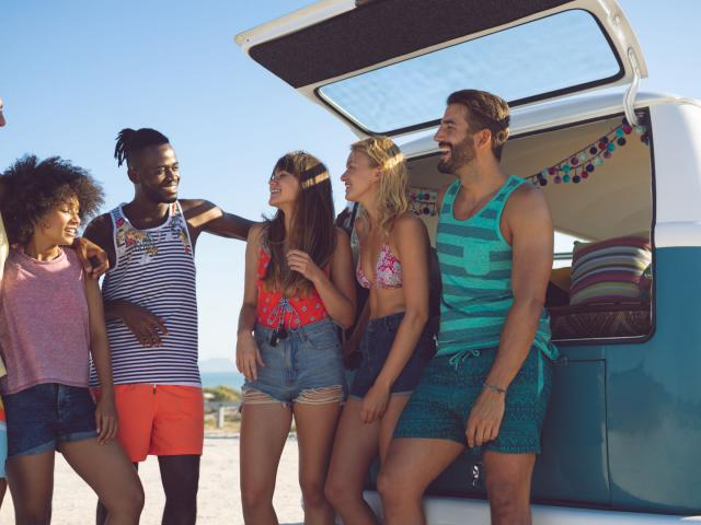 Group of friends interacting with each other near camper van at beach