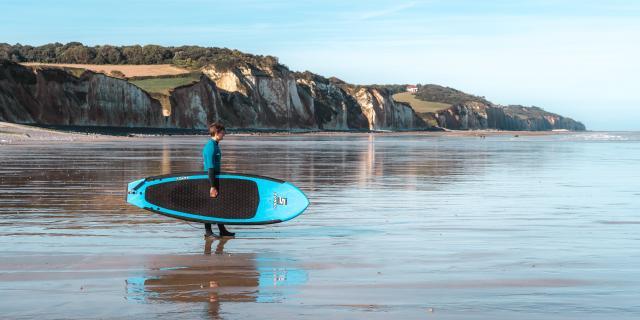 Jeune surfeur face aux falaises