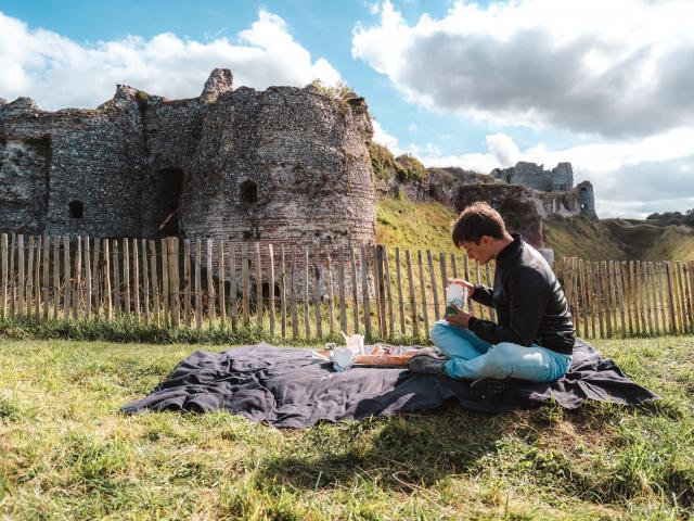 Jeune homme en train de pique-niquer devant le château d'Arques-la-Bataille