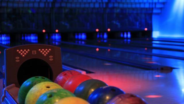 Boules de bowling de toutes les couleurs devant la piste plongée dans la pénombre