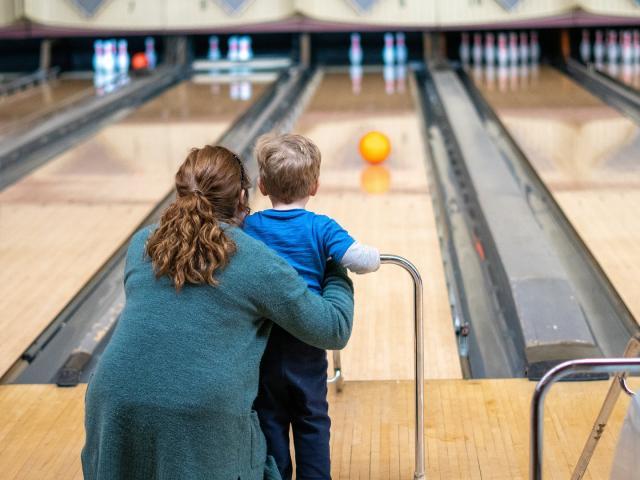 Une femme et un enfant viennent de lancer une boule sur une piste de bowling