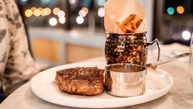 Assiette avec une viande rouge, des frites et une sauce.