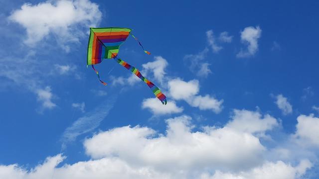 Cerf-volant triangulaire multicolore volant dans un ciel bleu