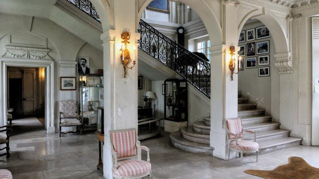 Hall d'entrée du Château de Miromesnil, arches blanches, escalier, meubles d'époque