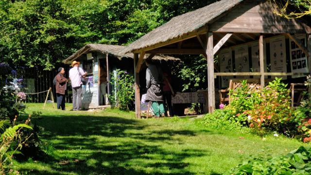 Cabane en bois de l'accueil du jardin. Préau en bois avec panneaux explicatifs