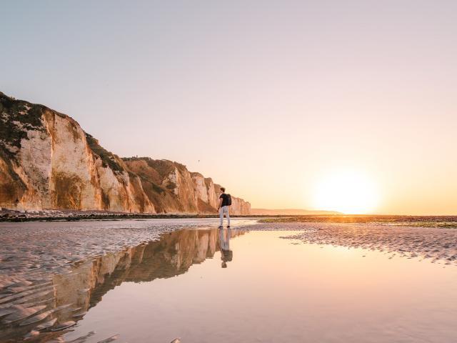Jeune homme regardant les falaises depuis la plage de Dieppe à marée basse durant le coucher de soleil