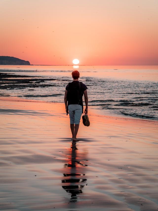 Jeune homme marchant sur la plage de Dieppe à marée basse durant le coucher de soleil