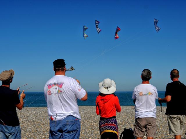 5 personnes font voler des cerfs-volants au-dessus des galets de la plage de Dieppe