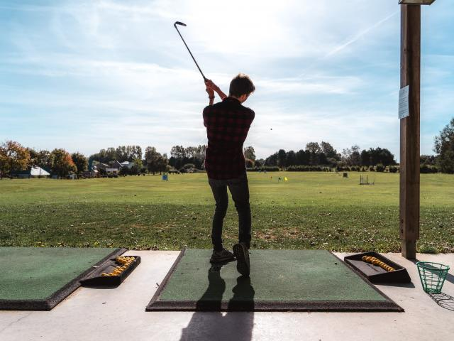 Jeune homme de dos en train de jouer au golf