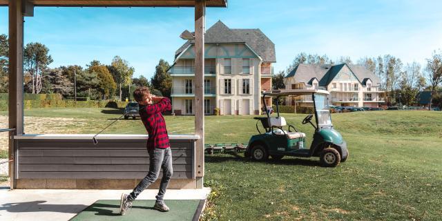 Golfette et jeune homme jouant au golf