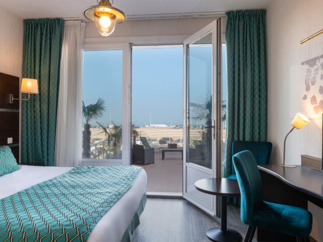 Chambre contemporaine aux tons turquoises avec une terrasse vue sur mer