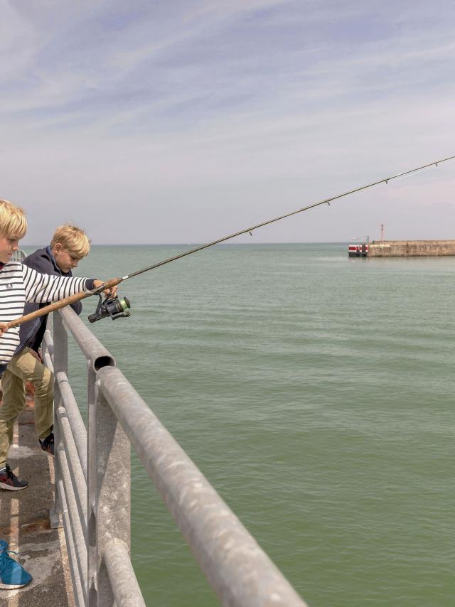 Deux jeunes garçons pêchant avec une canne sur la jetée
