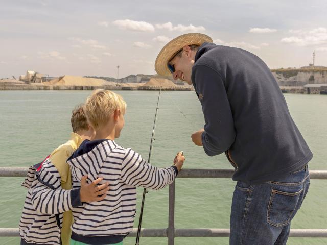 Deux jeunes garçons écoutent un homme leur prodiguer des conseils sur la jetée de Dieppe