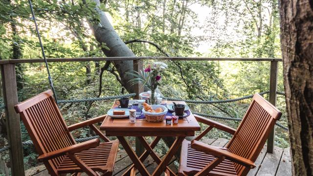 Table avec petit déjeuner sur un balcon d'une cabane dans les arbres en forêt