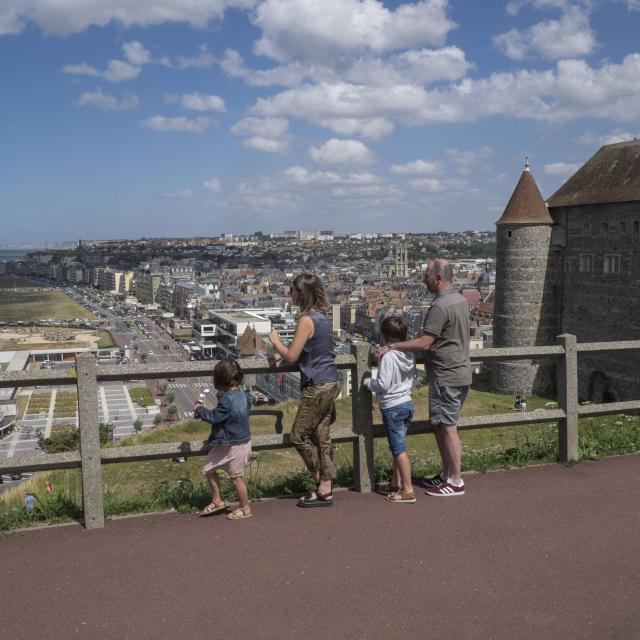 Un couple, un petit garçon et une petite fille de dos admirant le panorama sur la ville et la plage depuis l'esplanade du Château de Dieppe