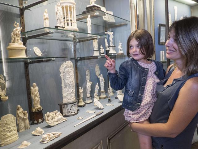 Une maman porte sa fille dans les bras pour qu'elle puisse admirer une vitrine présentant des sculptures en ivoire