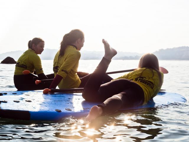 3 jeunes filles assises ou allongées sur des paddles devant un coucher de soleil