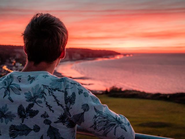 Jeune homme de dos regardant le soleil se coucher sur la plage de Pourville-sur-Mer
