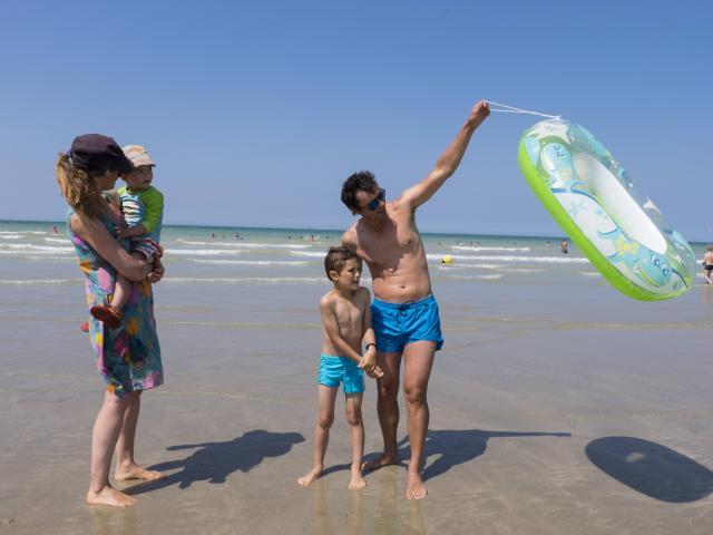 Famille de 4 personnes en maillot de bain sur la plage de Pourville à marée basse. Le papa soulève une bouée.