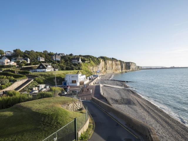 Point de vue sur la plage de Puys où l'on aperçois les falaises beiges recouvertes de vert, la plage de galets et la mer.