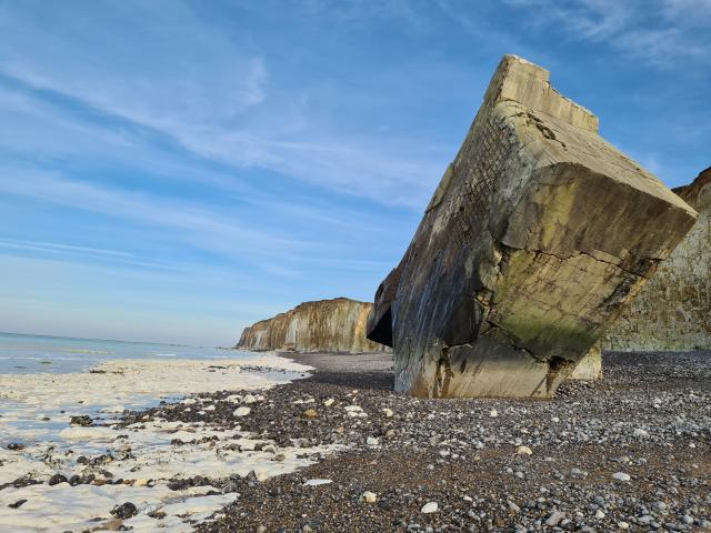 Bunker planté par angle dans la plage. Vue sur les falaises à l'arrière-plan