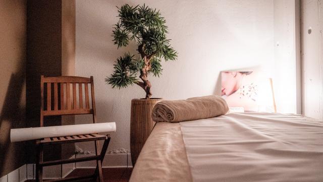 Table de massage avec une serviette posée dessus, une chaise et une plante.