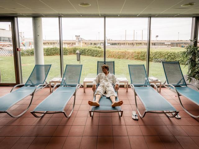 Jeune homme en peignoir se reposant sur un fauteuil au spa