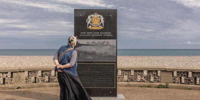 Une dame âgée lit le texte d'une stèle en marbre noir, mer et galets en arrière-plan