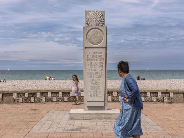 Une passante regarde la stèle en pierre grise, mer et galets en arrière-plan