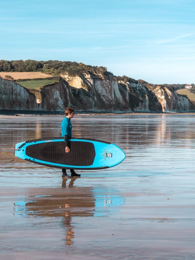 Jeune homme avec une planche de surf sur la plage de Pourville-sur-Mer à marée basse regardant au loin vers la mer