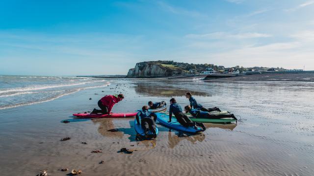 Moniteur donnant un cours de surf à cinq élèves