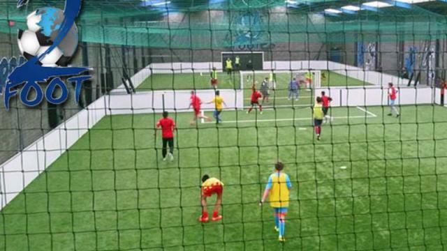 Match de football en intérieur vue à travers les filets du gardien